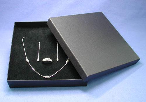 Schmuckschachtel aus Pappe, mit geripptem Krativ-Papier überzogen, mit Einlage aus besamtetem Schaumstoff mit Universalstanzung für Collier, Ohrschmuck und Ring, schwarz, Maße163x163x26 mm.